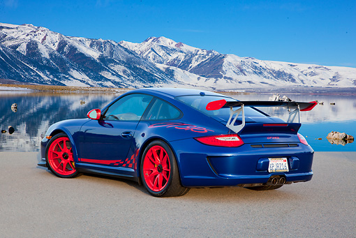 POR 04 RK0920 01 © Kimball Stock 2011 Porsche GT3 RS Blue And Red 3/4 Rear View On Pavement By Water And Snowy Mountains