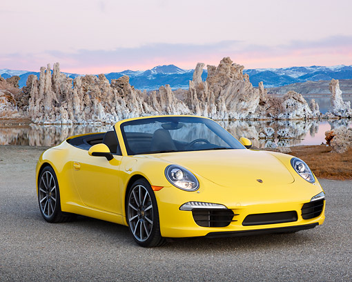 POR 04 RK0945 01 © Kimball Stock 2013 Porsche 911 Carrera S Cabriolet Yellow 3/4 Front View On Pavement By Water And Mountains