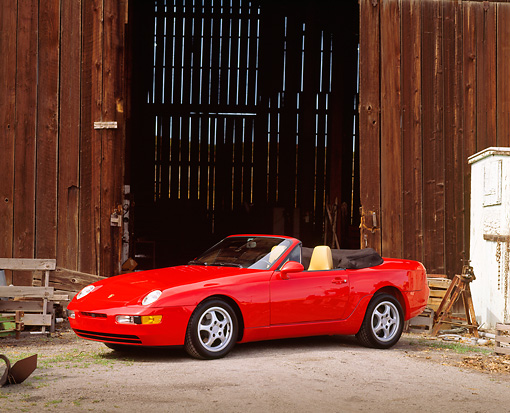 POR 04 RK0050 01 © Kimball Stock 1992 Porsche 968 Convertible Red 3/4 Side View By Barn