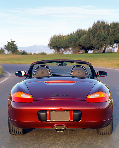 POR 04 RK0101 01 © Kimball Stock 1997 Porsche Boxster Convertible Burgundy Rear Shot On Pavement By Trees