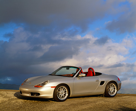POR 04 RK0194 05 © Kimball Stock 1998 Porsche Boxster Convertible Silver 3/4 Side View On Pavement Gray Clouds Blue Sky