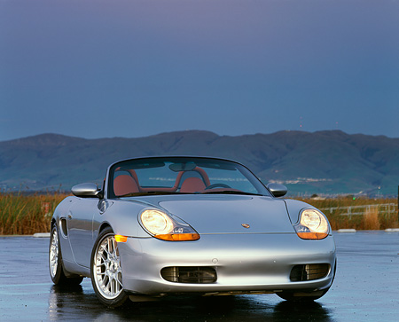 POR 04 RK0200 02 © Kimball Stock 1998 Porsche Boxster Convertible Silver 3/4 Front View On Pavement Mountains Background