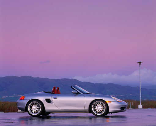 POR 04 RK0201 04 © Kimball Stock 1998 Porsche Boxster Convertible Silver Low Profile On Wet Pavement Tall Grass & Mts In Background Headlights On