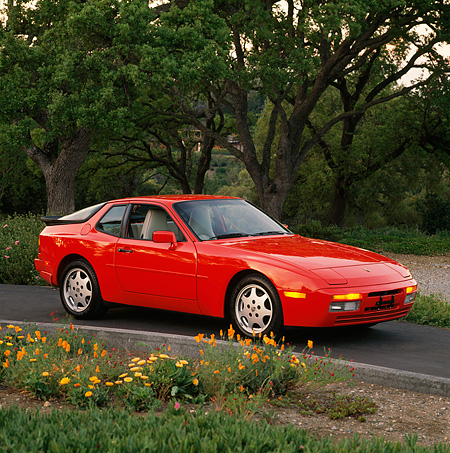 POR 04 RK0252 06 © Kimball Stock 1990 Porsche 944 Turbo Red Side 3/4 View On Pavement By Flowers And Trees Parking Lights On
