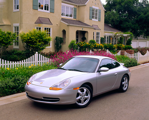 POR 04 RK0372 15 © Kimball Stock 1999 Porsche 911 Carrera Coupe Silver 3/4 Front View On Pavement By House