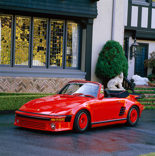 POR 04 RK0410 02 © Kimball Stock 1988 Porsche Convertible Custom Red 3/4 Front View On Driveway By House