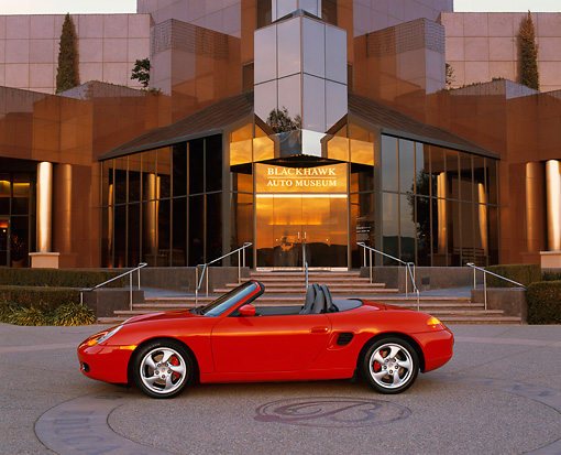 POR 04 RK0422 05 © Kimball Stock 2000 Porsche Boxster S Convertible Red Profile In Front Of Museum At Dusk