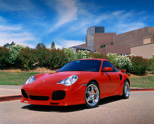 POR 04 RK0495 02 © Kimball Stock 2003 Porsche Turbo X-50 Red Low 3/4 Front View On Pavement Bushes Background