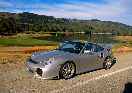 POR 04 RK0554 03 © Kimball Stock 2004 Porsche X50 Turbo Silver 3/4 Front View On Road By Water And Trees