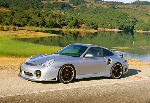 POR 04 RK0560 02 © Kimball Stock 2002 Porsche 996 Turbo Silver 3/4 Front View On Road By Water And Trees