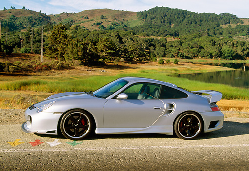 POR 04 RK0561 05 © Kimball Stock 2002 Porsche 996 Turbo Silver Profile View On Road By Water And Trees