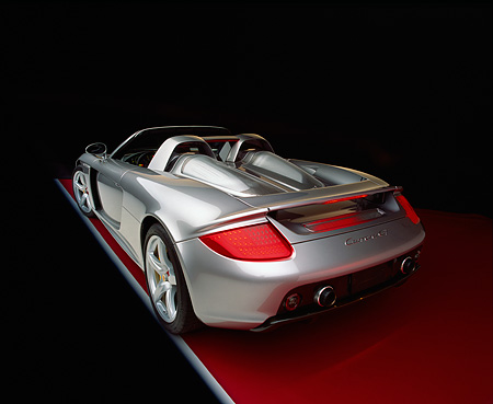 POR 04 RK0567 06 © Kimball Stock 2004 Porsche Carrera GT  Silver 3/4 Rear View On Red Floor Studio