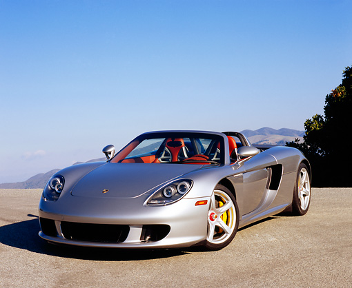 POR 04 RK0577 03 © Kimball Stock 2005 Porsche Carrera GT Convertible Silver 3/4 Front View On Pavement Hill