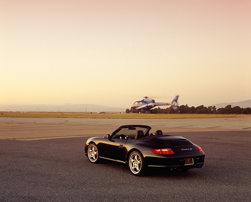 POR 04 RK0615 02 © Kimball Stock 2005 Porsche 911 S Carrera Convertible Black 3/4 Rear View On Pavement Helicopter In Flight Filtered