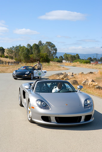 POR 04 RK0646 01 © Kimball Stock 2005 Porsche Boxster S Police Car Watching 2005 Porsche Carerra GT Silver Drive Away On Road