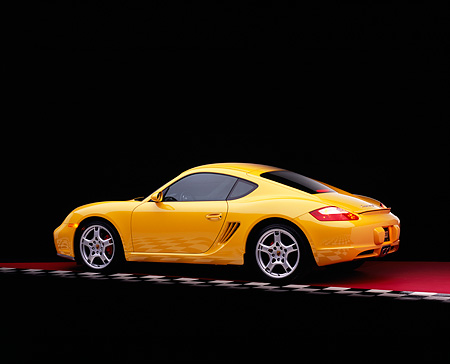 POR 04 RK0650 01 © Kimball Stock 2006 Porsche Cayman S Yellow 3/4 Rear View On Red Checkered Floor Studio