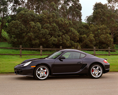 POR 04 RK0657 02 © Kimball Stock 2006 Porsche Cayman S Black Side 3/4 View On Pavement By Trees And Grass