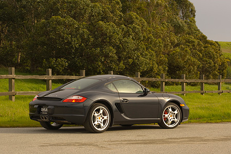 POR 04 RK0661 01 © Kimball Stock 2006 Porsche Cayman S Black Rear 3/4 View On Pavement By Fence Grass And Trees