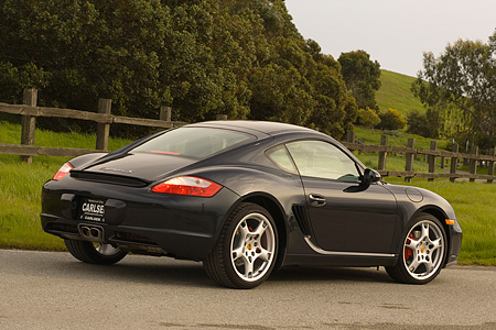 POR 04 RK0662 01 © Kimball Stock 2006 Porsche Cayman S Black Rear 3/4 View On Pavement By Fence Grass And Trees