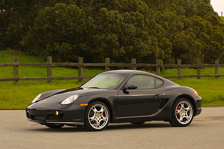 POR 04 RK0663 01 © Kimball Stock 2006 Porsche Cayman S Black Front 3/4 View On Pavement By Fence Grass And Trees