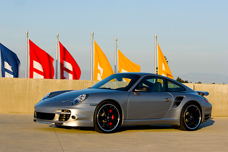 POR 04 RK0669 01 © Kimball Stock 2007 Porsche 911 Turbo Silver 3/4 Side View On Pavement By Flags