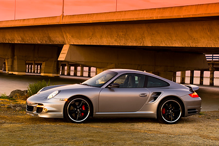 POR 04 RK0675 01 © Kimball Stock 2007 Porsche 911 Turbo Silver 3/4 Front View By Bridge And Water At Sunset