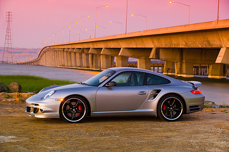 POR 04 RK0678 01 © Kimball Stock 2007 Porsche 911 Turbo Silver 3/4 Front View By Bridge And Water At Sunset