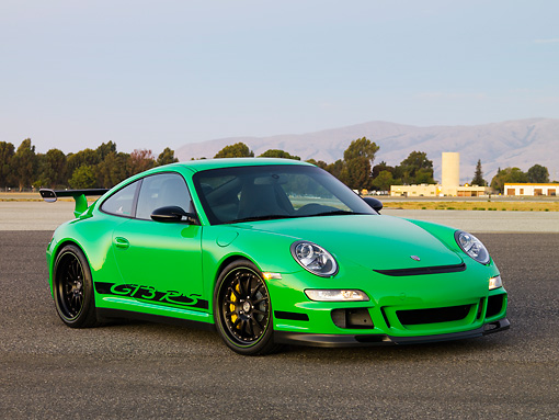POR 04 RK0764 01 © Kimball Stock 2007 Porsche 911 GT3 RS Green 3/4 Front View On Pavement By Trees Mountain Sky Buildings