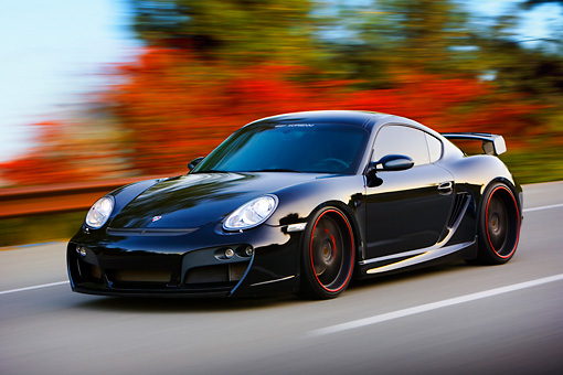 POR 04 RK0795 01 © Kimball Stock 2008 Porsche Cayman S TechArt Black 3/4 Front View Driving By Foliage