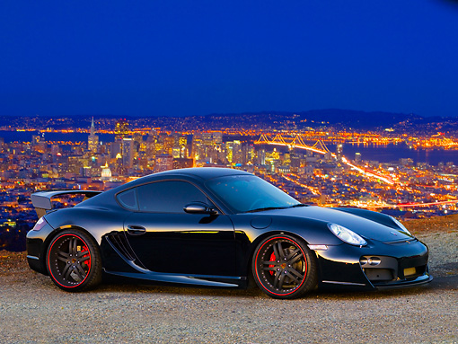 POR 04 RK0802 01 © Kimball Stock 2008 Porsche Cayman S TechArt Black 3/4 Front View On Pavement City Lights