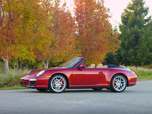 POR 04 RK0823 01 © Kimball Stock 2009 Porsche 911 Carrera 4S Convertible Red 3/4 Front View On Pavement By Trees