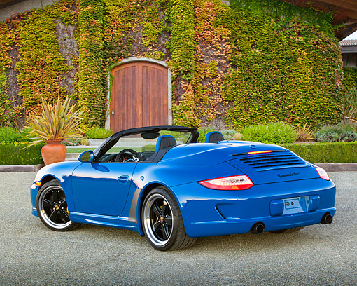 POR 07 RK0130 01 © Kimball Stock 2011 Porsche 911 Speedster Convertible Blue 3/4 Rear View On Gravel By Ivy Covered Building
