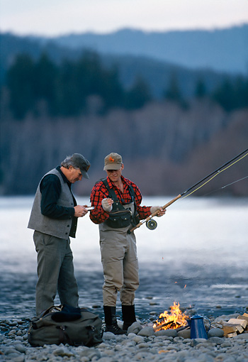 REC 04 DS0005 01 © Kimball Stock Two Fishermen Standing By Fire On Rocky Lake Shore