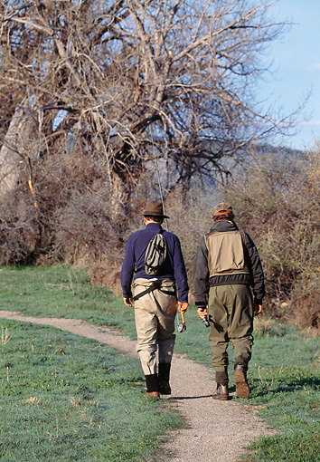REC 04 DS0006 01 © Kimball Stock Two Fishermen Walking Down Trail Carrying Fishing Rods