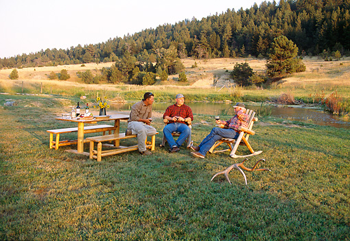 REC 05 DS0001 01 © Kimball Stock Three Men Sitting By Picnic Table And Creek