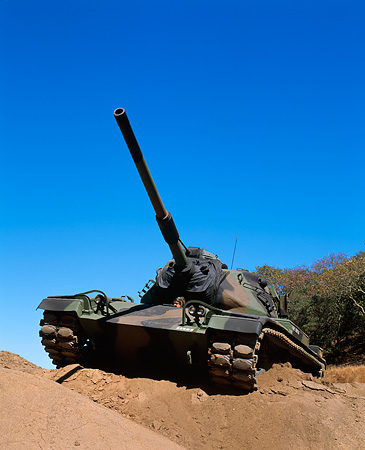 TNK 01 RK0006 04 © Kimball Stock Camouflage M-60 Tank 3/4 Front View On Dirt Hill By Tree Blue Sky