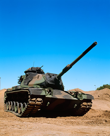 TNK 01 RK0007 11 © Kimball Stock Camouflage M-60 Tank 3/4 Front View On Dirt By Tree Blue Sky