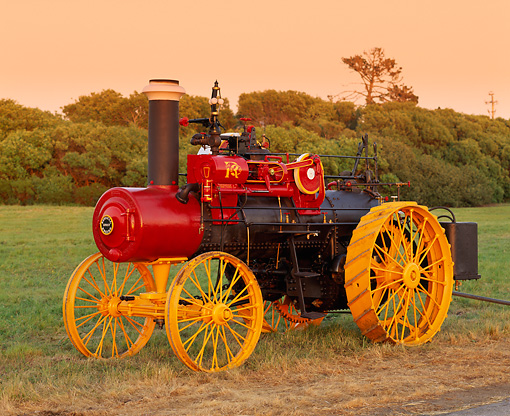 TRA 01 RK0001 06 © Kimball Stock 1905 Russell Steam Tractor Side 3/4 View On Grass Trees At Dusk