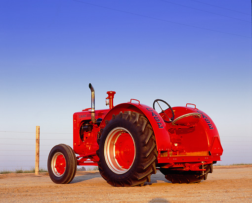 TRA 01 RK0054 01 © Kimball Stock 1947 LA Case Red Tractor 3/4 Rear View On Dirt Blue Sky