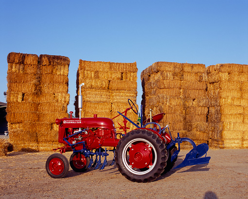 TRA 01 RK0060 02 © Kimball Stock 1948 Farmall Cub Red Tractor Side View On Dirt By Stacks Of Hay