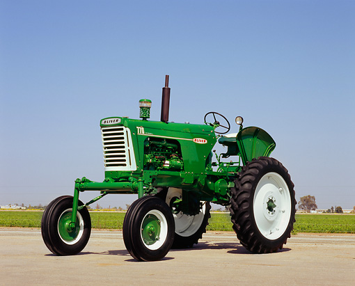 TRA 01 RK0072 05 © Kimball Stock 1955 Oliver High Crop Green And White Tractor 3/4 Front View On Pavement Blue Sky