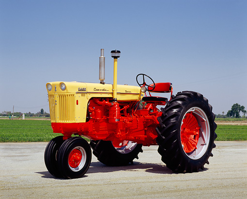 TRA 01 RK0078 02 © Kimball Stock 1958 Case 801-B Caseomatic Yellow And Red Tractor 3/4 Front View On Pavement Blue Sky