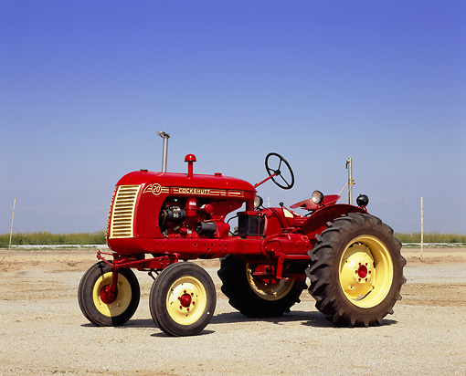 TRA 01 RK0079 01 © Kimball Stock 1953 Cockshutt 20 Red And Yellow Tractor 3/4 Side View On Dirt