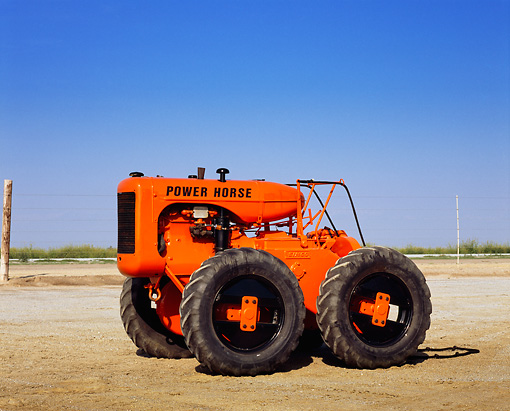 TRA 01 RK0090 05 © Kimball Stock 1937 Eimco Power Horse Tractor Orange 3/4 Side View On Dirt Blue Sky