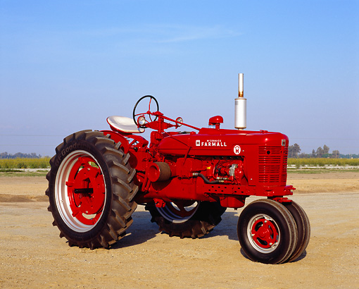 TRA 01 RK0096 01 © Kimball Stock 1954 Farmall Super H Red Tractor 3/4 Side View On Dirt Blue Sky
