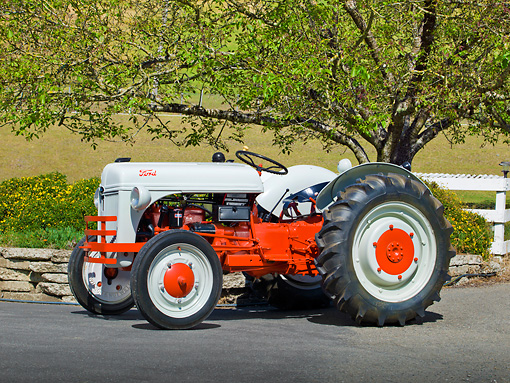 TRA 01 RK0130 01 © Kimball Stock 1939 Ford 9N Tractor White And Red 3/4 Side View On Pavement By Fence And Trees