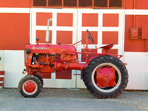 TRA 01 RK0138 01 © Kimball Stock 1957 McCormick Cub Tractor Red Profile View On Gravel By Barn