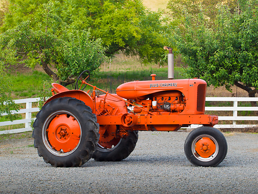 TRA 01 RK0139 01 © Kimball Stock 1946 Allis-Chalmers WD Tractor Orange Profile View On Gravel By Fence And Trees