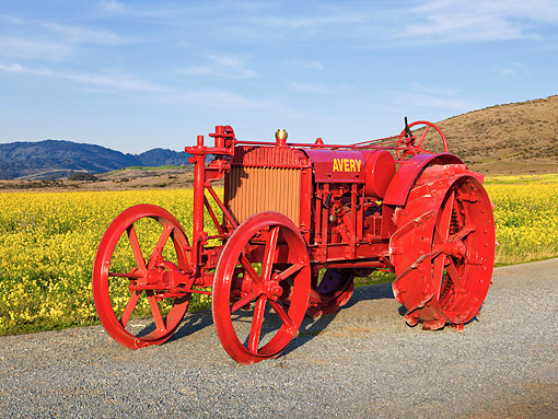 TRA 01 RK0142 01 © Kimball Stock 1918 Avery Model B Tractor Orange 3/4 Front View On Gravel By Field Of Wildflowers