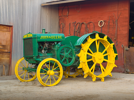 TRA 01 RK0159 01 © Kimball Stock 1925 John Deere Model D Green And Yellow 3/4 Side View On Dirt By Shed